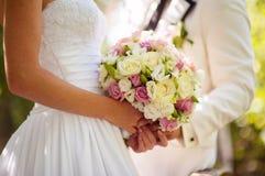 婚礼在新娘手上开花花束有在背景的白色礼服的 库存照片