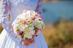 婚礼在新娘手上开花花束有在背景的白色礼服的 免版税库存图片