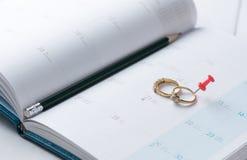 婚礼在日历的金戒指与铅笔 免版税库存照片