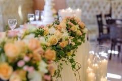 婚礼在灼烧的蜡烛背景的花的布置  免版税库存照片