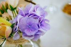 婚礼在玻璃花瓶的花花束在客人桌上 免版税库存照片