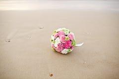 婚礼在美丽的沙子海滩的花束花 库存照片