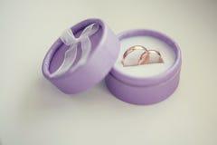 婚礼在紫色箱子的金戒指在白色背景 库存图片