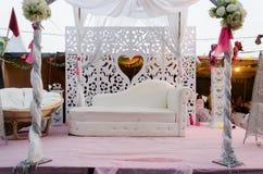 婚礼场面的装饰-一个白色沙发和一个屏幕有心脏的 免版税库存照片