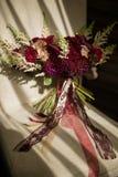 婚礼大花束在伯根地树荫下,装饰用绿色和丝带,在阳光下 库存照片