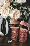 婚礼天鹅绒有发光的美丽的脚跟的桃红色鞋子有金子在白玫瑰花束,在黑暗的玉树旁边的婚戒的 免版税库存图片