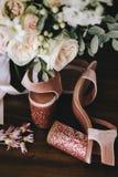 婚礼天鹅绒有发光的美丽的脚跟的桃红色鞋子有金子在白玫瑰花束,在黑暗的玉树旁边的婚戒的 图库摄影