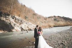 婚礼夫妇、拥抱的新郎和的新娘,室外近的河 免版税图库摄影