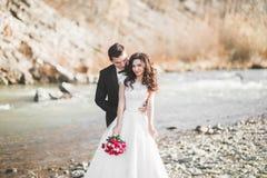 婚礼夫妇、拥抱的新郎和的新娘,室外近的河 免版税库存照片