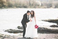 婚礼夫妇、拥抱的新郎和的新娘,室外近的河 免版税库存图片