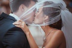 年轻婚礼夫妇亲吻。 库存图片