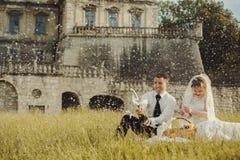 婚礼夫妇在一座老城堡的前面的草去野餐 库存图片
