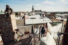 婚礼夫妇在老镇利沃夫州走,亲吻,爱 在屋顶上 库存照片