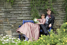 婚礼夫妇坐蓝色长凳 库存图片