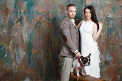 婚礼夫妇新娘和新郎塑造带着狗和手提箱的画象 免版税库存图片