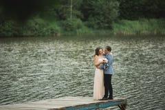 婚礼夫妇,新娘,走和摆在码头的新郎 免版税库存图片