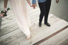 婚礼夫妇,新娘,走和摆在码头的新郎 库存照片