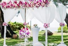 婚礼成拱形,五颜六色的花,花卉装饰,杉树,海背景 免版税库存图片