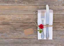 婚礼或华伦泰晚餐概念、桌设置与典雅的银色利器红色玫瑰花和空标识符 免版税库存图片