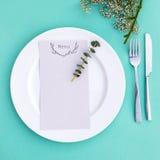 婚礼或豪华晚餐的晚餐菜单 表设置从上面 典雅的空的板材、利器和花 免版税库存照片