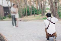 婚礼摄影师在夏天为在爱的夫妇照相本质上 图库摄影