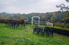 婚礼曲拱和椅子在观点在秋天 免版税库存照片