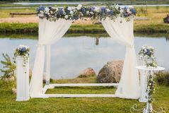 婚礼曲拱用蓝色花和白光丝绸装饰 夏天婚礼 免版税图库摄影