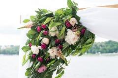 婚礼曲拱的部分与绿叶、牡丹和白色材料的 免版税图库摄影