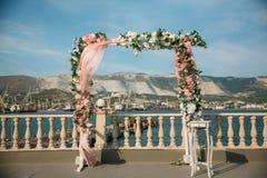 婚礼曲拱,用在草坪的花装饰的法坛 海和山在背景 免版税库存照片