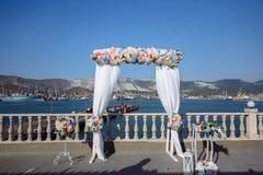 婚礼曲拱,用在草坪的花装饰的法坛 海和山在背景 免版税库存图片