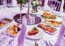 婚礼桌服务与鲜美饭食,开胃小菜盛肉盘冷盘,鱼盛肉盘,乳酪盛肉盘 假日宴会菜单 免版税库存照片
