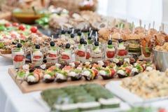 婚礼桌用食物 快餐和开胃菜在表上 鱼和生肉与菜 微型汉堡 免版税库存图片