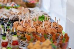 婚礼桌用食物 快餐和开胃菜在表上 鱼和生肉与菜 汉堡在焦点 库存图片