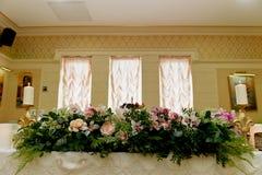 婚礼桌装饰新婚佳偶 在花桌上的歌曲  桃红色和白色调色板,上升了,兰花 免版税库存图片