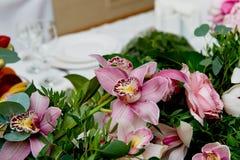 婚礼桌装饰新婚佳偶 在花桌上的歌曲  桃红色和白色调色板,上升了,兰花 库存图片