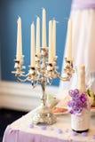 婚礼桌装饰:蜡烛和一个瓶香槟 库存图片