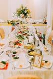 婚礼桌集合包括了不同的在桌安置的盘和巨大的花束 免版税库存图片