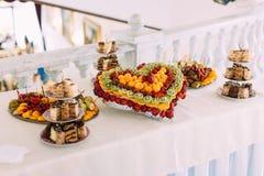 婚礼桌集合 以心脏的形式果子板材 免版税图库摄影