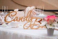 婚礼棒棒糖 在桌上的木题字 免版税库存照片