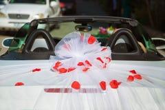 婚礼汽车后面视图和瓣在上面 用花装饰的豪华婚礼汽车 结婚的附属的标志和罐头 免版税库存照片