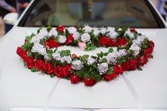 婚礼汽车和瓣在上面 用花装饰的豪华婚礼汽车 结婚的附属的标志和罐头 心脏玫瑰 免版税库存图片