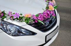 婚礼汽车的敞篷的一张详细的照片,装饰用许多不同的花 汽车为婚礼ceremon准备 免版税库存照片