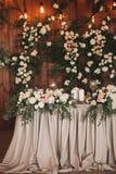 婚礼用花和植物装饰的桌宴会,在木背景的减速火箭的灯 免版税图库摄影
