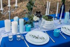 婚礼用蛋糕、利器有器皿板材的和蜡烛装饰的宴会桌在一张蓝色桌布 免版税库存图片