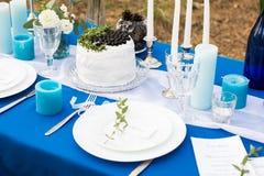 婚礼用蛋糕、利器有器皿的和蜡烛装饰的宴会桌在一张蓝色桌布 库存照片