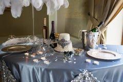 婚礼用蛋糕和蜡烛装饰的宴会桌在一张蓝色桌布 免版税库存图片
