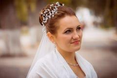 婚礼礼服和新娘花束的美丽的新娘,有婚礼花的愉快的新婚佳偶有婚礼构成的妇女,妇女和头发 库存照片