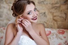 婚礼礼服和面纱的一个好女孩广泛地投入耳环和微笑 有大蓝眼睛的新娘,白色甚而 免版税库存图片