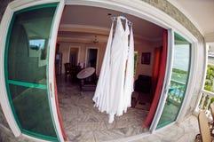 婚礼礼服在水池、海洋和山的背景的旅馆 库存照片