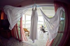 婚礼礼服在水池、海洋和山的背景的旅馆 库存图片